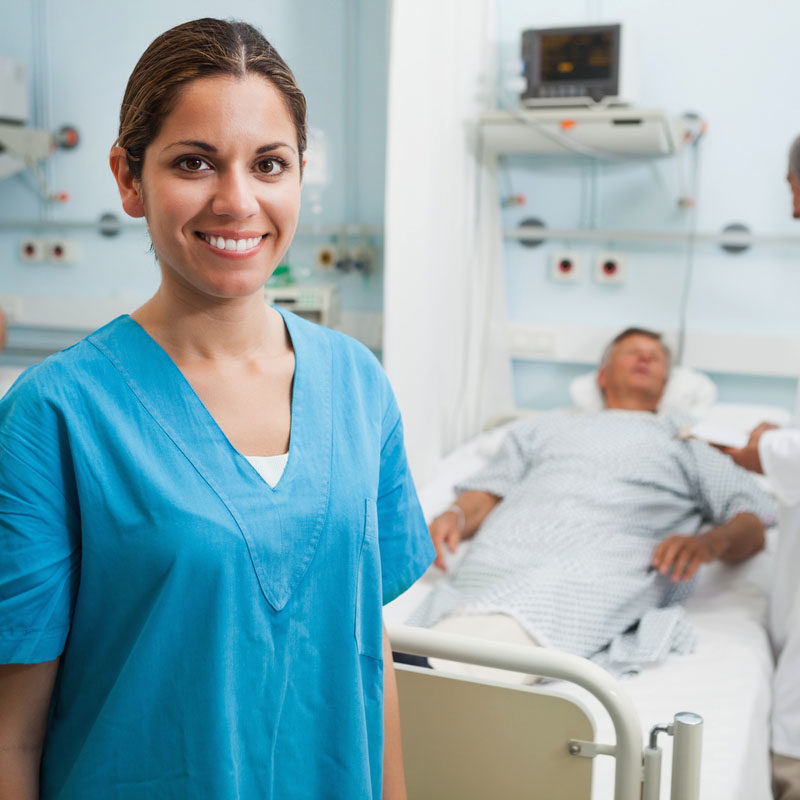 Happy nurse standing in hospital room with doctor and patient talking in background
