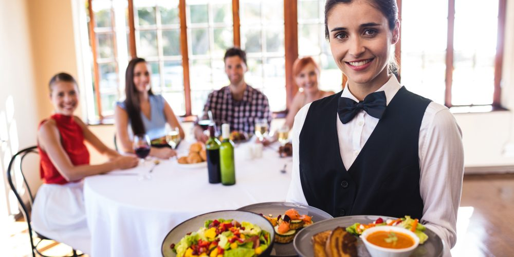 Portrait,Of,Waitress,Holding,Food,On,Plate,In,Restaurant